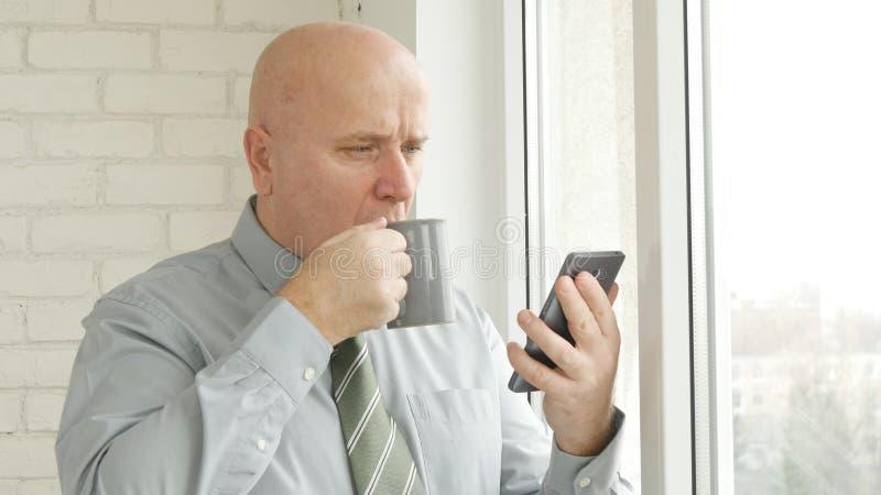Homem de negócios Read um texto do telefone celular e para beber um copo do chá imagens de stock royalty free
