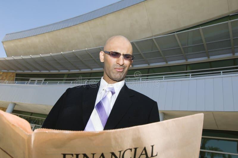 Homem de negócios Reading um jornal financeiro fotos de stock royalty free