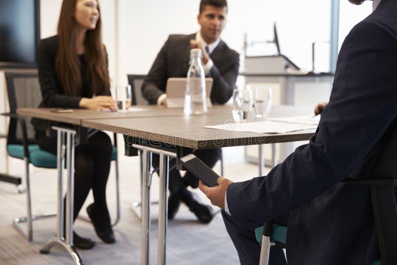 Homem de negócios Receiving Text Message durante a reunião fotografia de stock