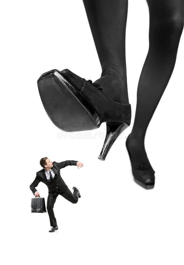 Homem de negócios receoso que funciona longe de um pé grande fotografia de stock