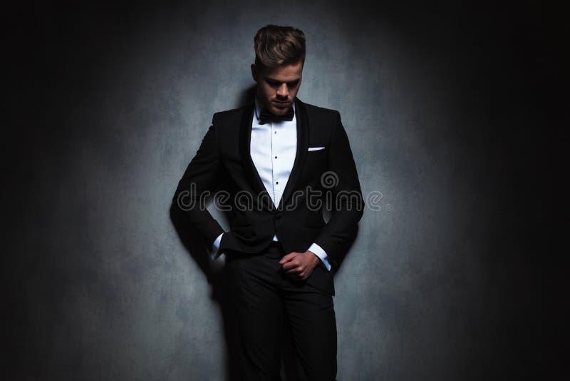 Homem de negócios relaxado que inclina-se contra uma parede preta ao olhar d fotos de stock royalty free