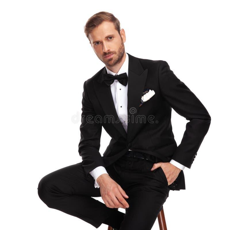 Homem de negócios relaxado que senta-se na cadeira de madeira e que guarda bolsos fotos de stock royalty free
