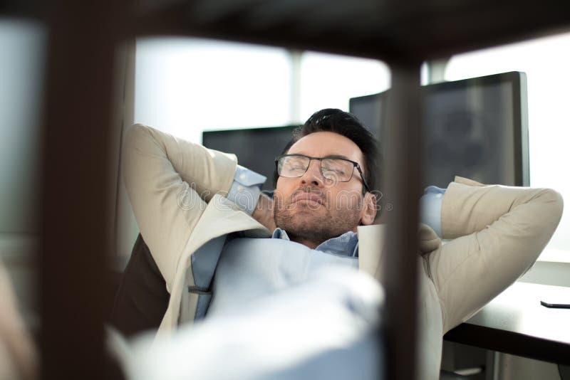 Homem de negócios de relaxamento que senta-se em sua mesa foto de stock