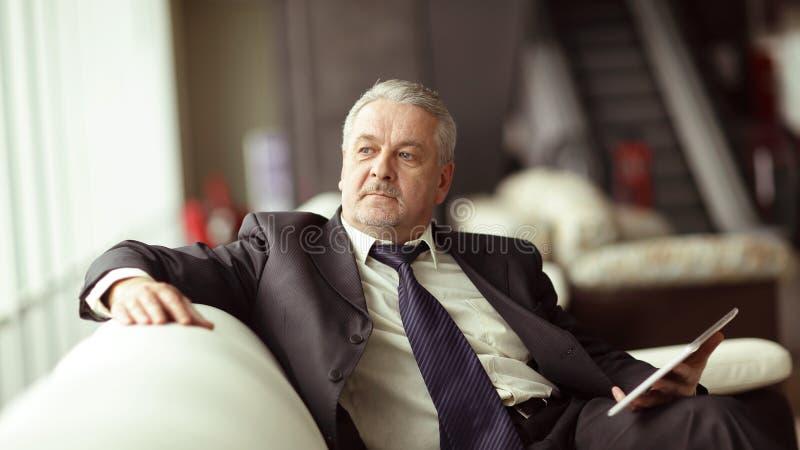 Homem de negócios responsável que senta-se no escritório moderno Povos e tecnologia imagem de stock