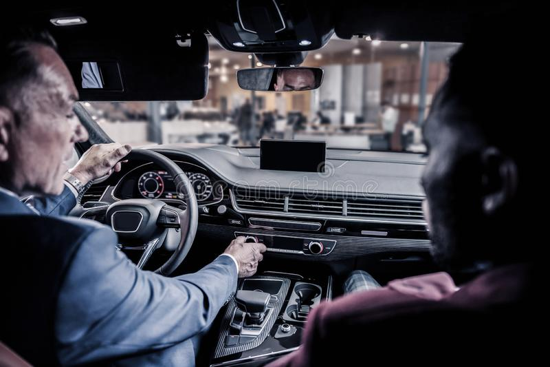 Homem de negócios rico maduro que senta-se atrás da roda de seu carro futuro imagens de stock royalty free