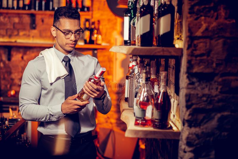 Homem de negócios rico que possui a barra que olha garrafas do álcool fotos de stock