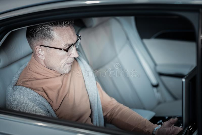 Homem de negócios rico que trabalha no portátil ao sentar-se na parte de trás do carro fotografia de stock