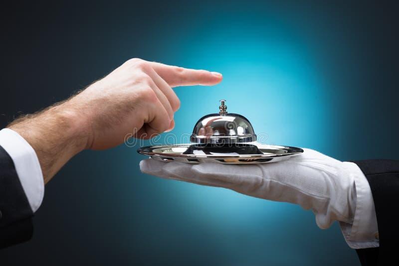 Homem de negócios Ringing In Service Bell guardada pelo mandarete fotografia de stock