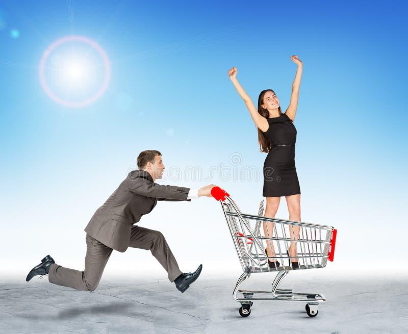 Homem de negócios running com a menina no carrinho de compras imagens de stock