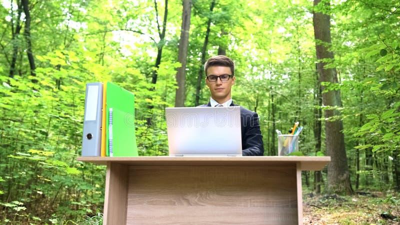 Homem de negócios sério no terno que trabalha no portátil na mesa de escritório no ar fresco da floresta fotos de stock royalty free