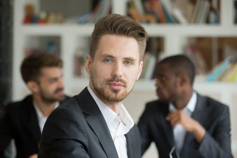 Homem de negócios sério novo que olha a câmera na reunião, headshot foto de stock royalty free