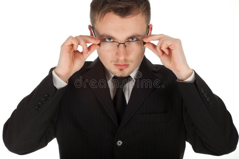 Homem de negócios sério que corrige vidros fotos de stock