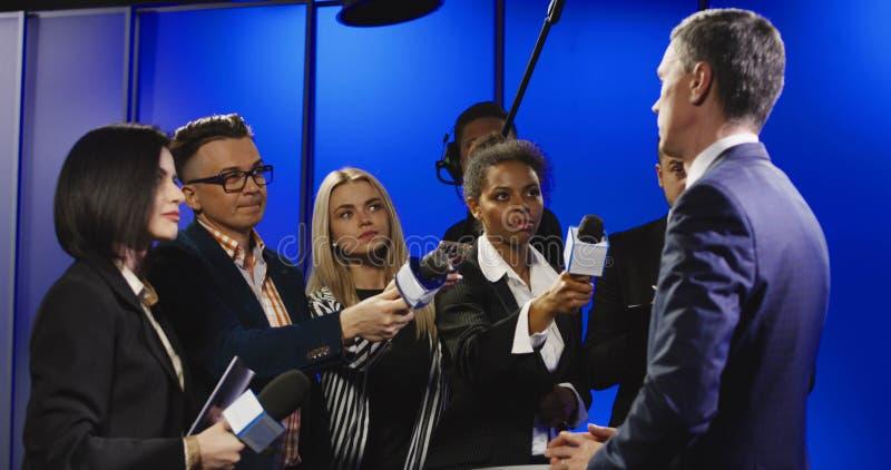 Homem de negócios sério que fala aos representantes dos mass media imagem de stock royalty free