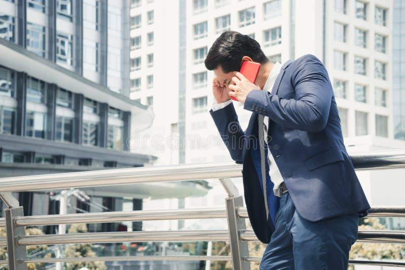Homem de negócios sério que fala no telefone celular vermelho na cidade o conceito da falha de negócio e as vendas diminuíram imagem de stock