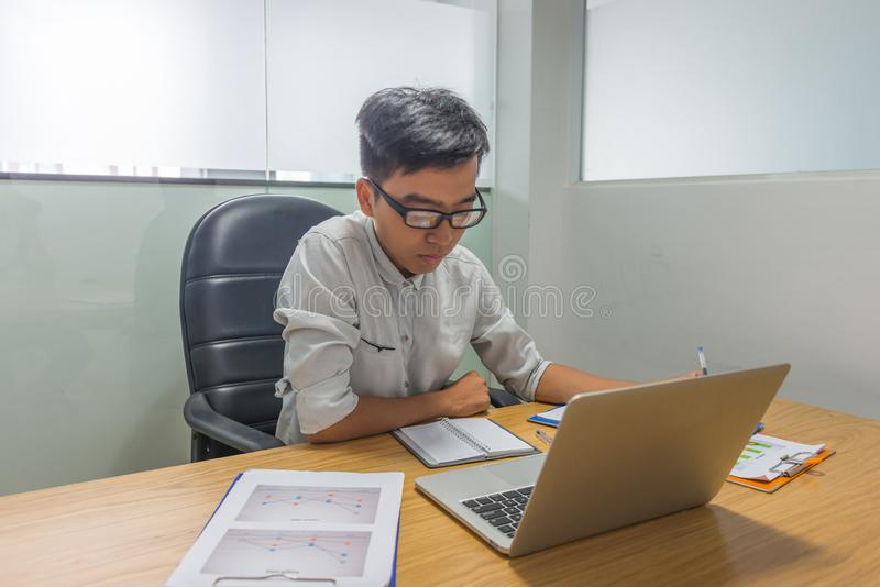 Homem de negócios sério que lê o documento financeiro no escritório fotografia de stock
