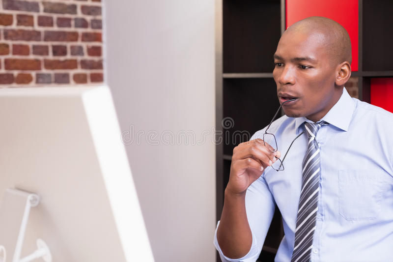 Homem de negócios sério que olha o monitor do computador fotos de stock royalty free