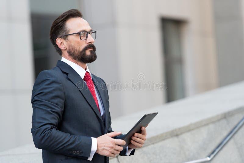 Homem de negócios sério que olha pensativamente no quando da distância que está sozinho fotos de stock royalty free