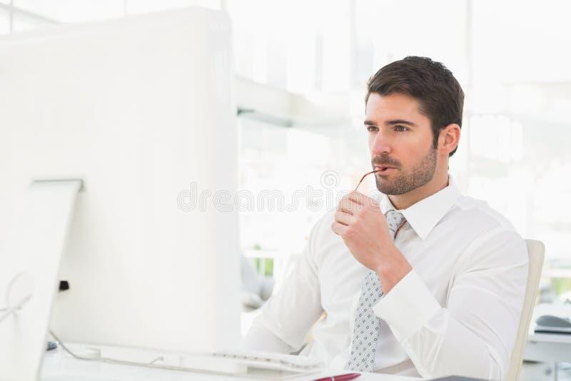 Homem de negócios sério que usa o monitor do computador fotografia de stock