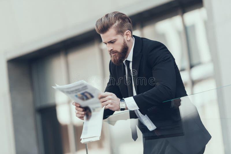 Homem de negócios sério Reading Newspaper Outdoor imagem de stock royalty free