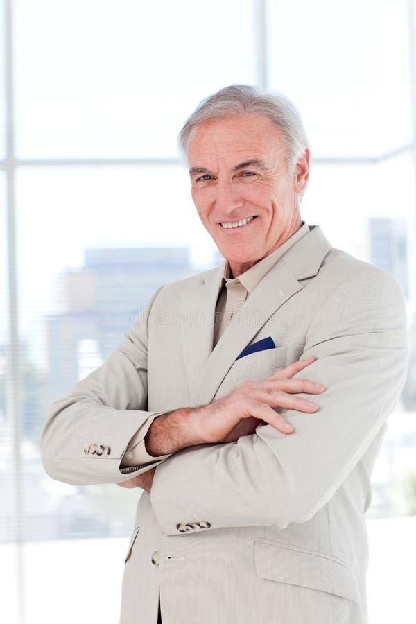 Homem de negócios sênior atrativo com braços dobrados foto de stock
