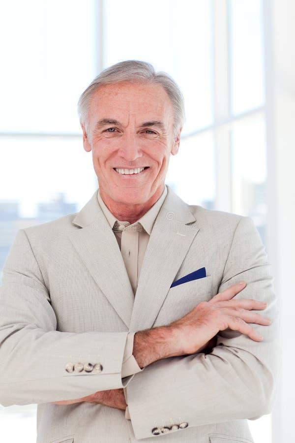 Homem de negócios sênior confiável com braços dobrados fotografia de stock