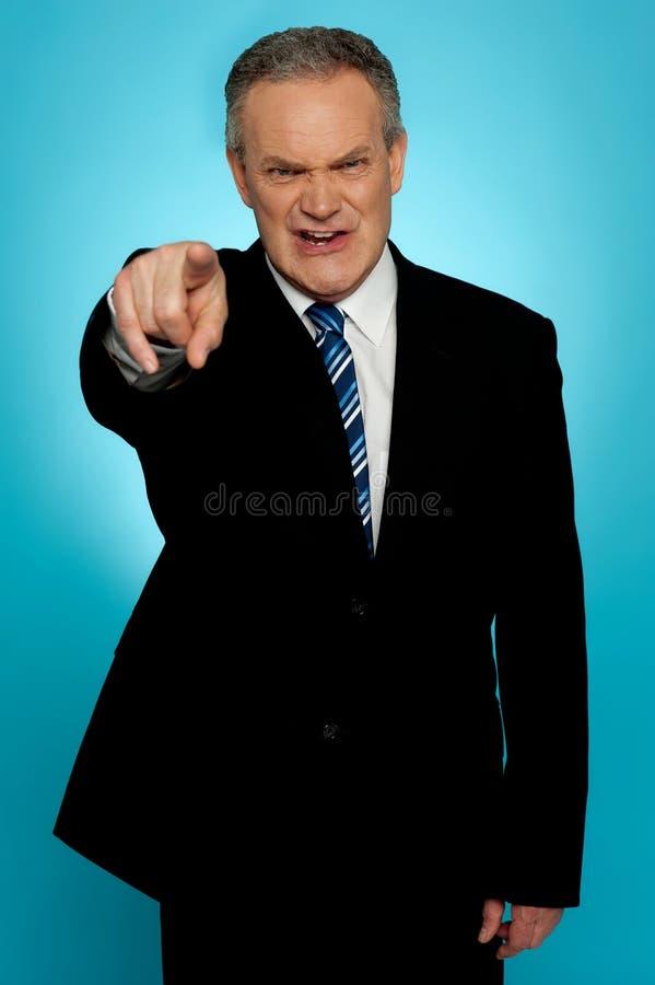 Homem de negócios sênior irritado que aponta o dedo em você fotografia de stock