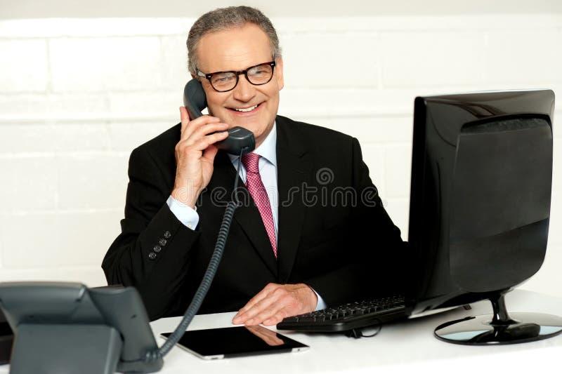 Homem de negócios sênior que atende ao atendimento de telefone fotografia de stock