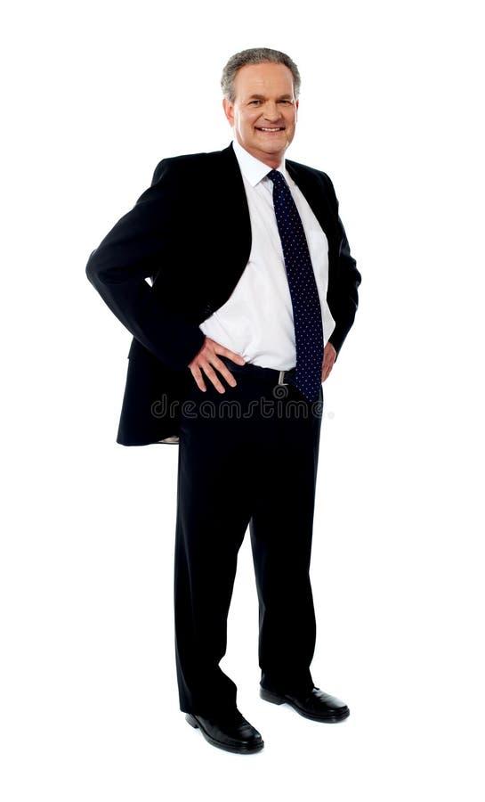 Homem de negócios sênior que levanta com mãos em sua cintura imagem de stock royalty free