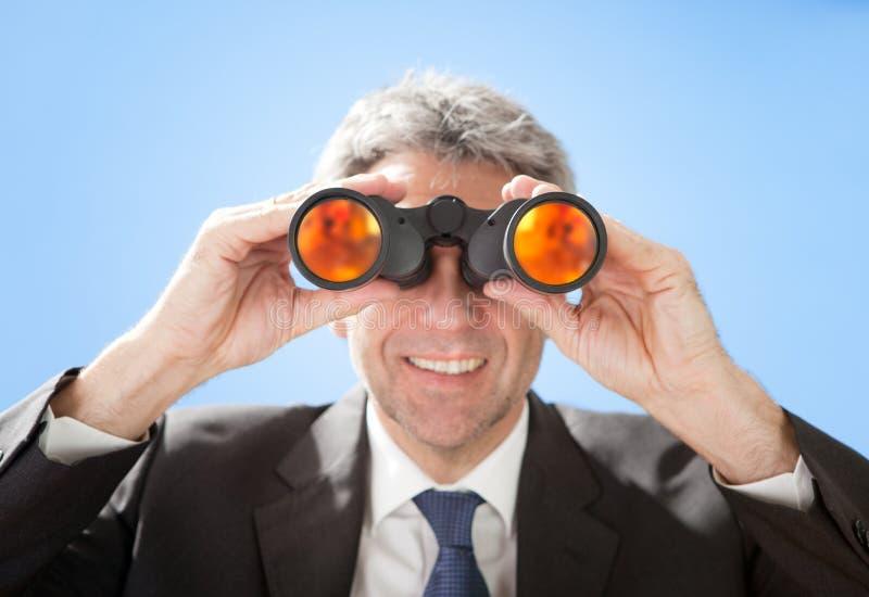 Homem de negócios sênior que olha através dos binóculos foto de stock