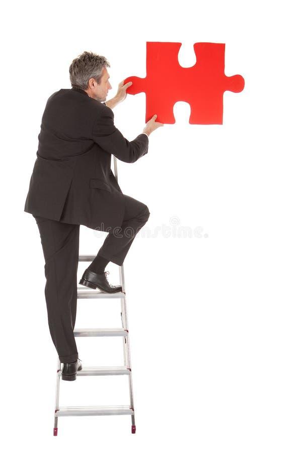 Homem de negócios sênior que prende um enigma de serra de vaivém imagens de stock royalty free