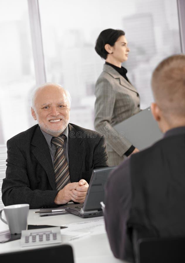 Homem de negócios sênior que sorri no trabalho imagens de stock