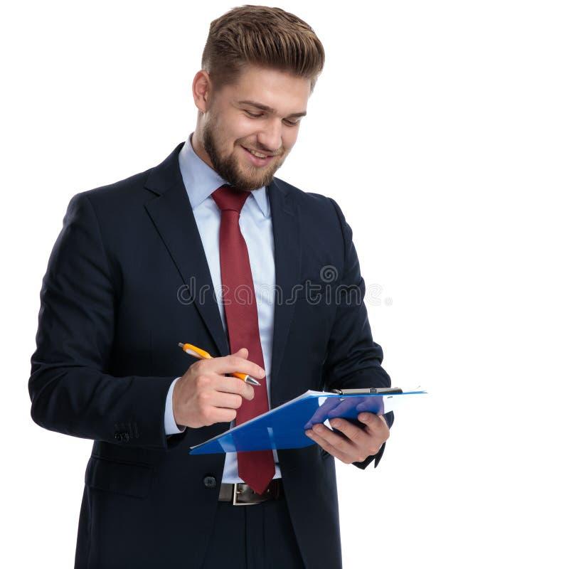 Homem de negócios seguro aproximadamente a escrever em sua prancheta imagens de stock royalty free