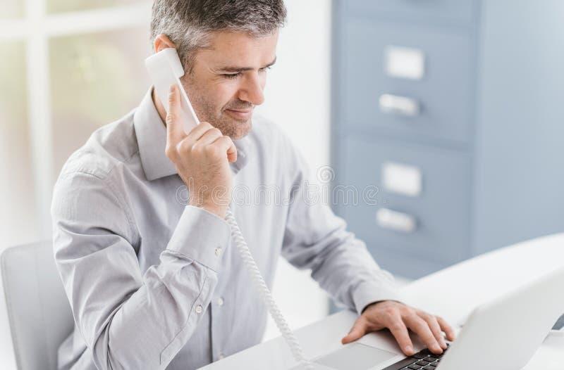 Homem de negócios seguro e consultante de sorriso que trabalham em seu escritório, está tendo um telefonema: conceito de uma comu fotografia de stock