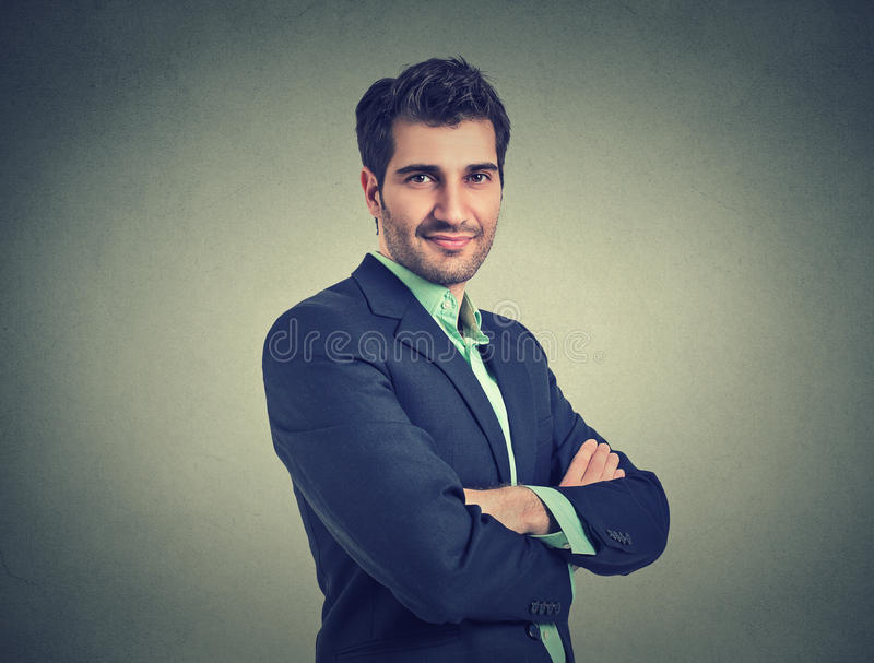 Homem de negócios seguro isolado no fundo cinzento da parede fotos de stock