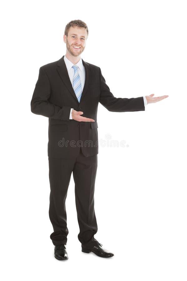 Homem de negócios seguro que dá boas-vindas sobre o fundo branco imagem de stock royalty free
