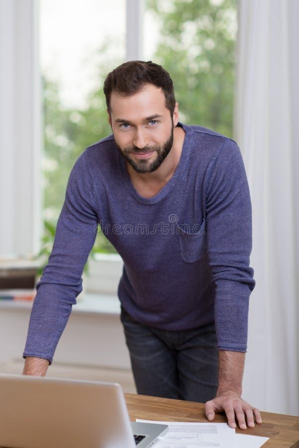 Homem de negócios seguro que inclina-se em sua mesa fotografia de stock royalty free