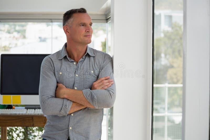 Homem de negócios seguro que olha através da janela ao inclinar-se na parede imagens de stock