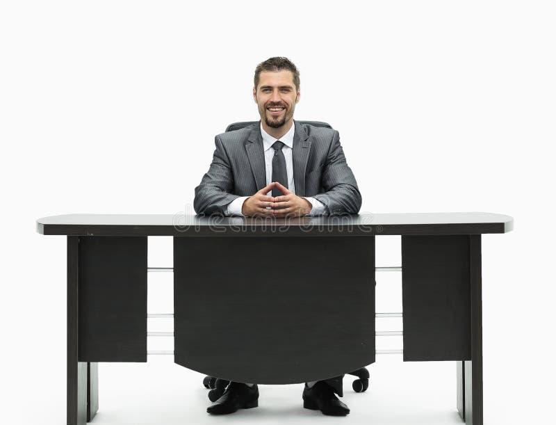 homem de negócios seguro que senta-se atrás de uma mesa Isolado no branco fotografia de stock royalty free