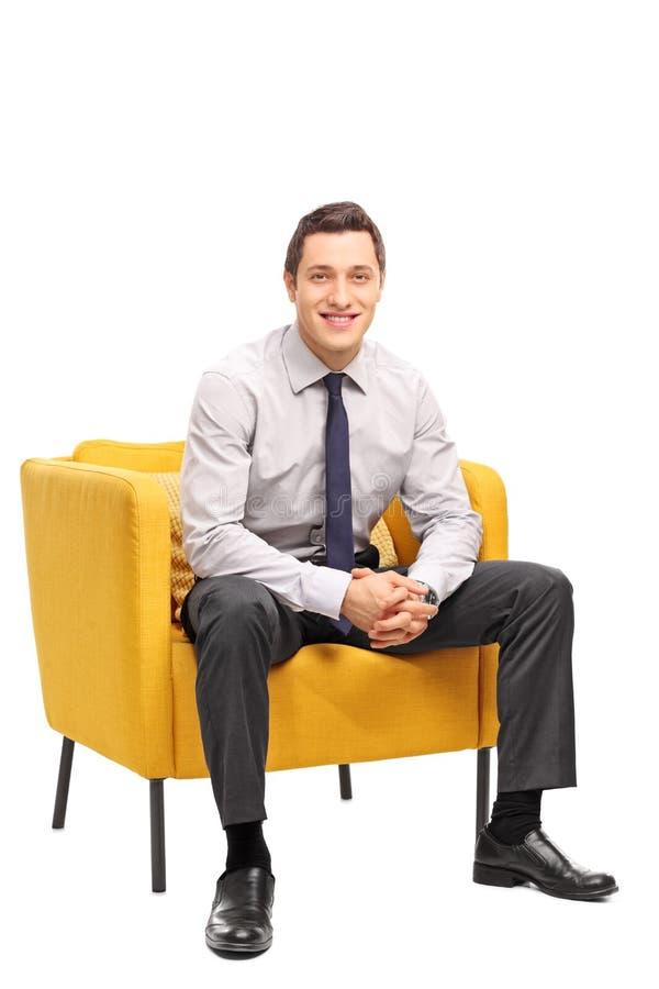 Homem de negócios seguro que senta-se em uma poltrona fotografia de stock royalty free