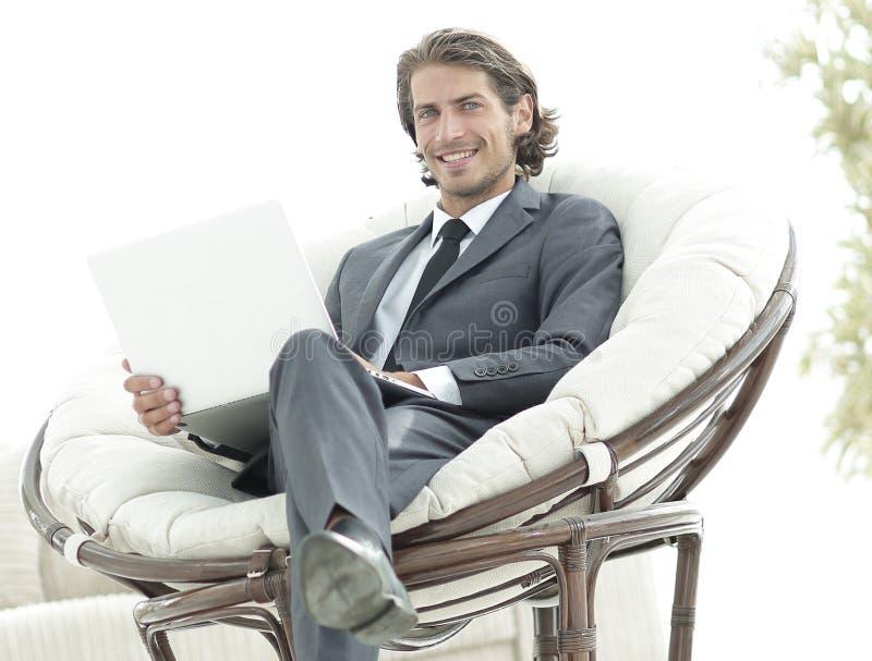 Homem de negócios seguro que trabalha com o portátil que senta-se na poltrona confortável fotografia de stock