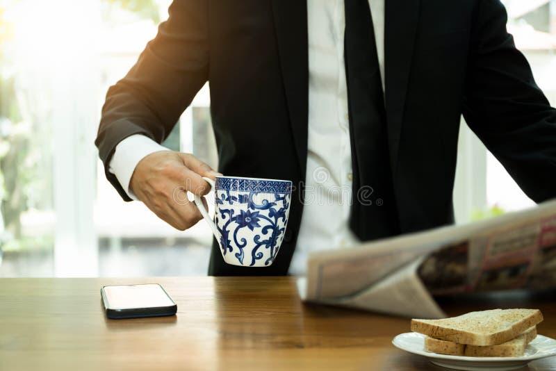 Homem de negócios selecionado da caneca de café do foco que tem o café da manhã e o readi imagem de stock royalty free