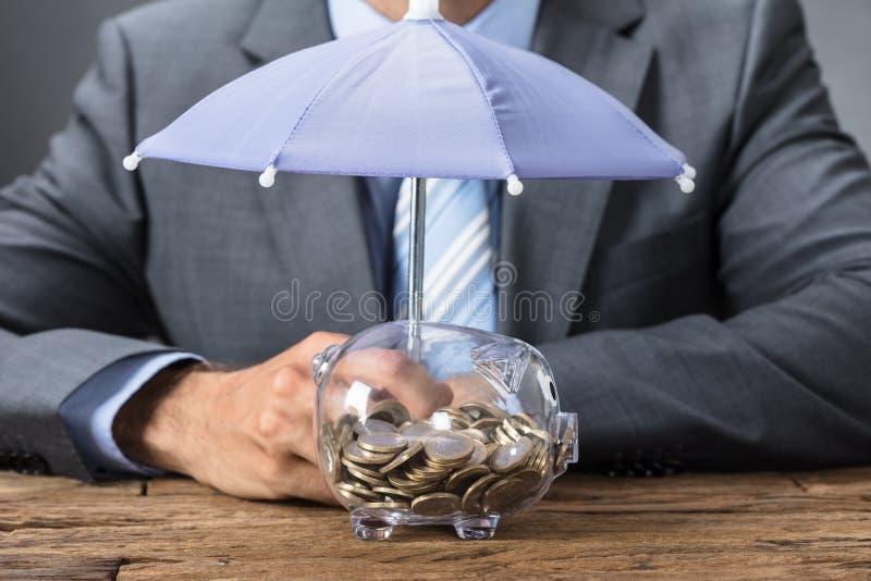 Homem de negócios Sheltering Transparent Piggybank com guarda-chuva imagem de stock royalty free