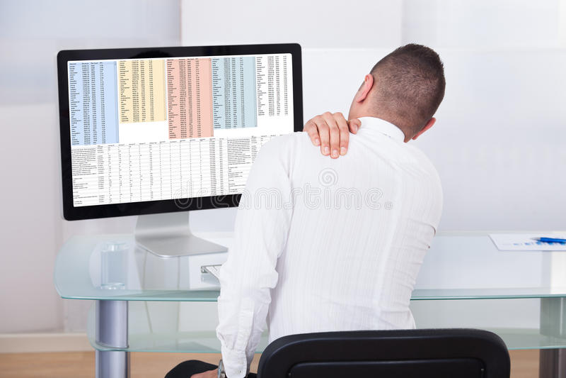 Homem de negócios With Shoulder Pain que usa o computador foto de stock