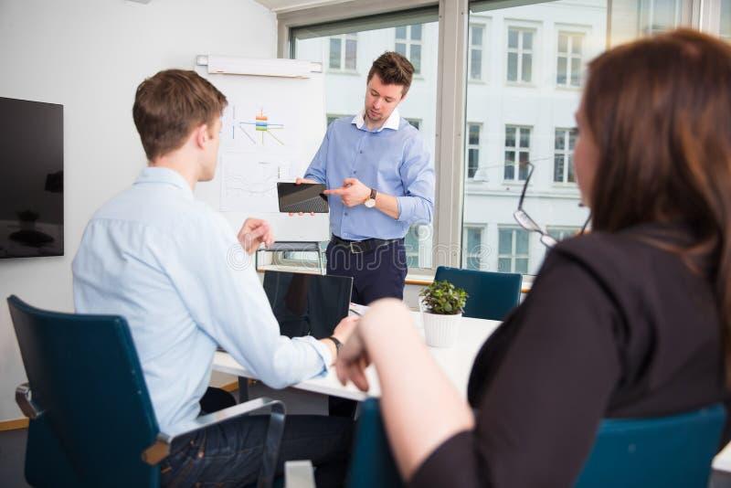 Homem de negócios Showing Tablet Computer aos colegas de trabalho fotografia de stock