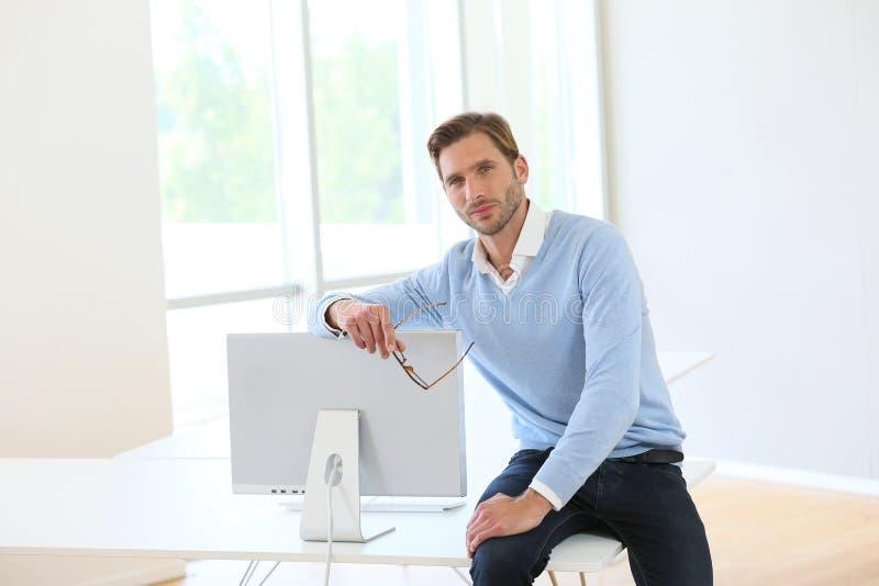 Homem de negócios Sitting On Desk fotografia de stock royalty free
