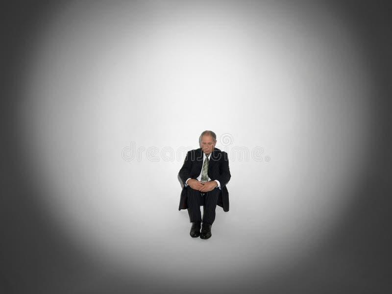 Homem de negócios Sitting In Spotlight fotografia de stock royalty free