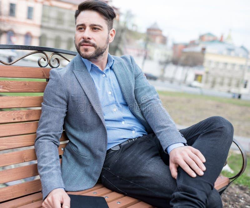 Homem de negócios Sitting At um banco de parque fotos de stock