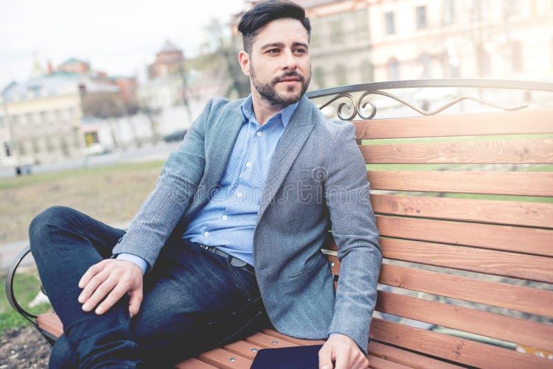 Homem de negócios Sitting At um banco de parque imagens de stock