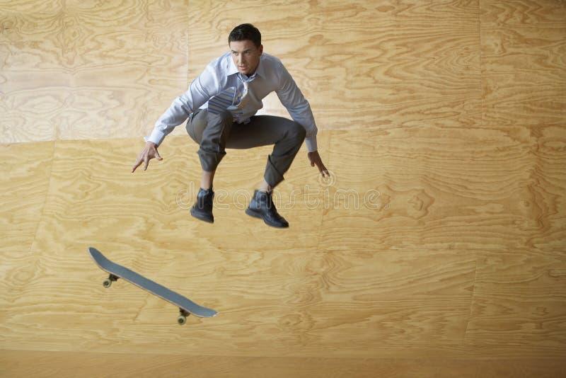 Homem de negócios With Skateboard Jumping contra o paneling de madeira foto de stock