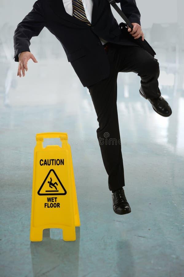 Homem de negócios Slipping no assoalho molhado fotografia de stock